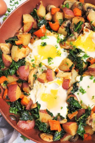 Country Veggie Breakfast Skillet made in a copper skillet with 4 sunny side eggs on top on a white surface