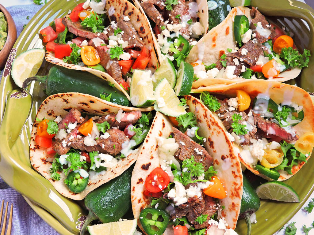 marinated steak street tacos in a golden tortilla topped with red and yellow grape tomatoes, cilantro, jalapenos, lime, and feta