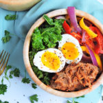 BBQ Pulled Pork Power Breakfast Bowl made with Byron's Pulled Pork BBQ, in a wooden bowl with kale, bell peppers, and a sliced soft boiled egg