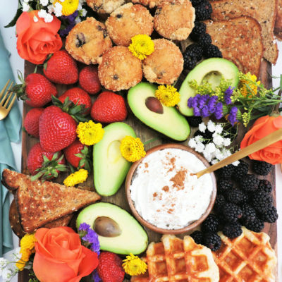 How to Make a Beautiful Charcuterie Brunch Board, perfect for Mother's Day, wooden board with mini blueberry muffins, toast, strawberries, blackberries, avocado, waffles, and fresh flowers