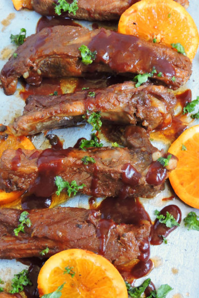 Slow Cooker Bourbon & Orange BBQ Ribs made with the Crock-Pot Express Crock on a platter with orange slices