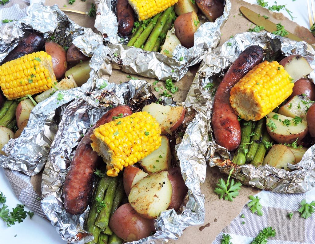 Cajun Grilled Sausage & Veggie Foil Packets, grilled corn, asparagus, red potatoes, and sausage in foil