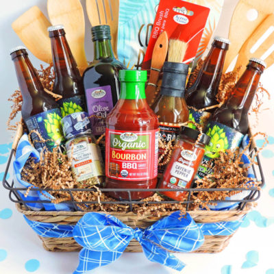 How to Make the Ultimate DIY Grilling Gift Basket for Dad, Happy Father's Day gift basket with BBQ items in a wicker basket with blue ribbon