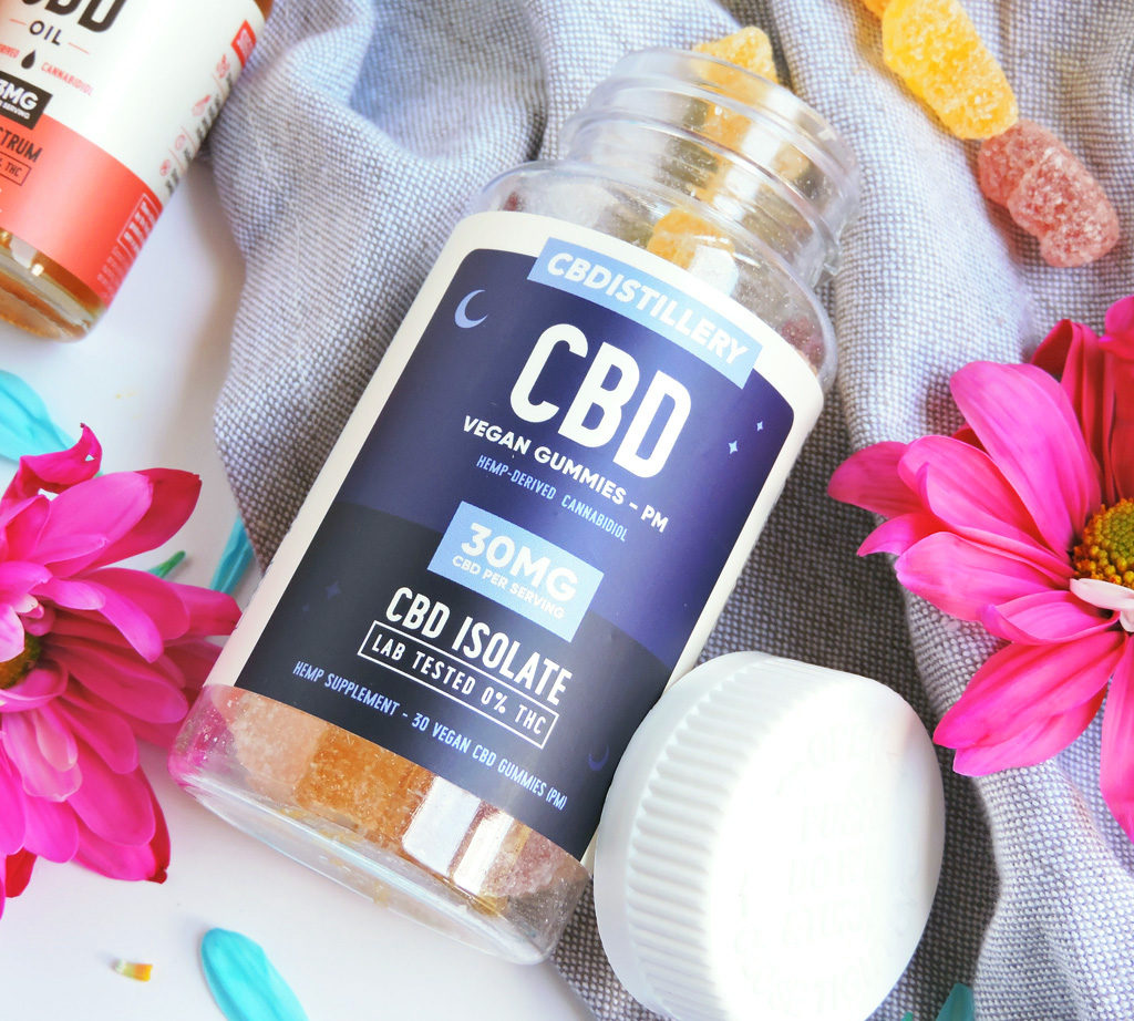 The Truth About CBD, CBD Oil Full Spectrum Tincture, CBD PM gummies, and CBD Topical Salve made by CBDistillery, on a white surface