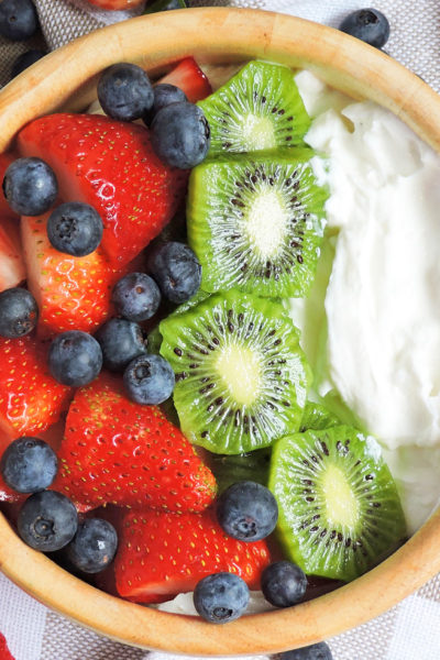 yogurt breakfast bowl made with 2% fage greek yogurt, topped with strawberries, blueberries, and kiwi