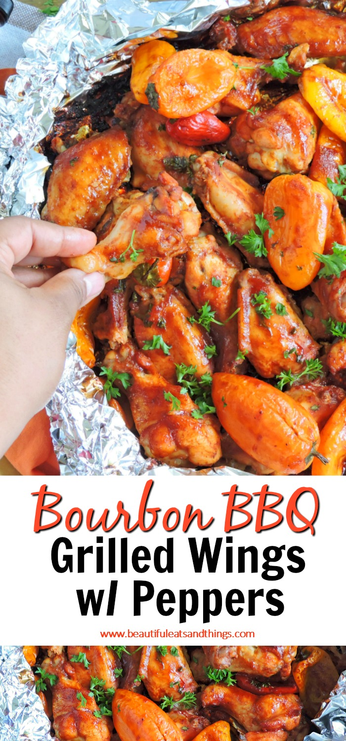 Bourbon BBQ Grilled Wings with Orange and Red Peppers in foil on a wooden surface