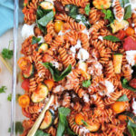 Veggie-Loaded Whole Wheat Pasta Bake in a glass casserole dish with basil leaves, ricotta and tomatoes on top
