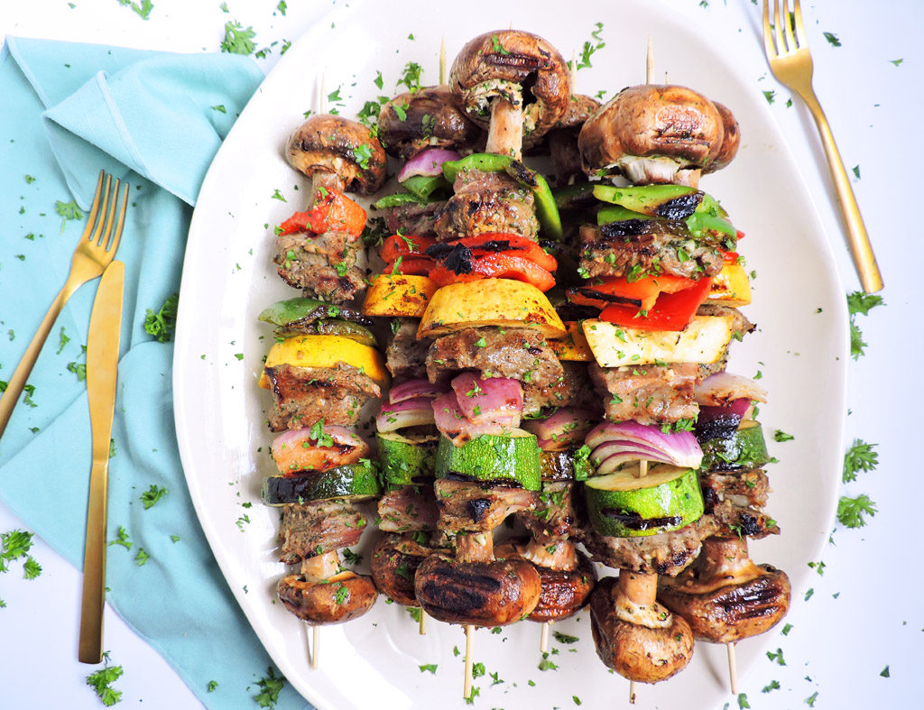 Zesty Italian Grilled Lamb Kabobs , American Lamb boneless lamb shoulder placed on wooden skewers with mushrooms, red, green, and yellow bell peppers, and onions