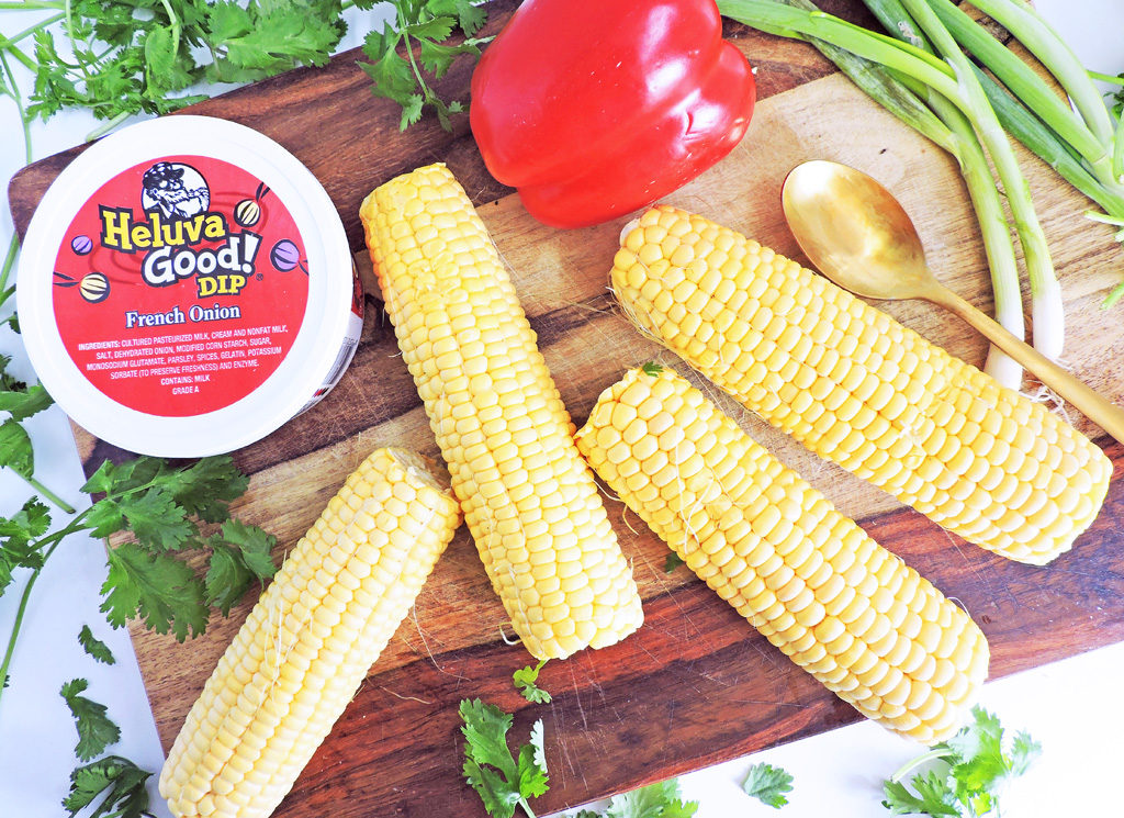 French Onion Grilled Corn Salad with red bell pepper, cilantro, green onions, Heluva Good! French Onion Dip, and cojita cheese in a white bowl