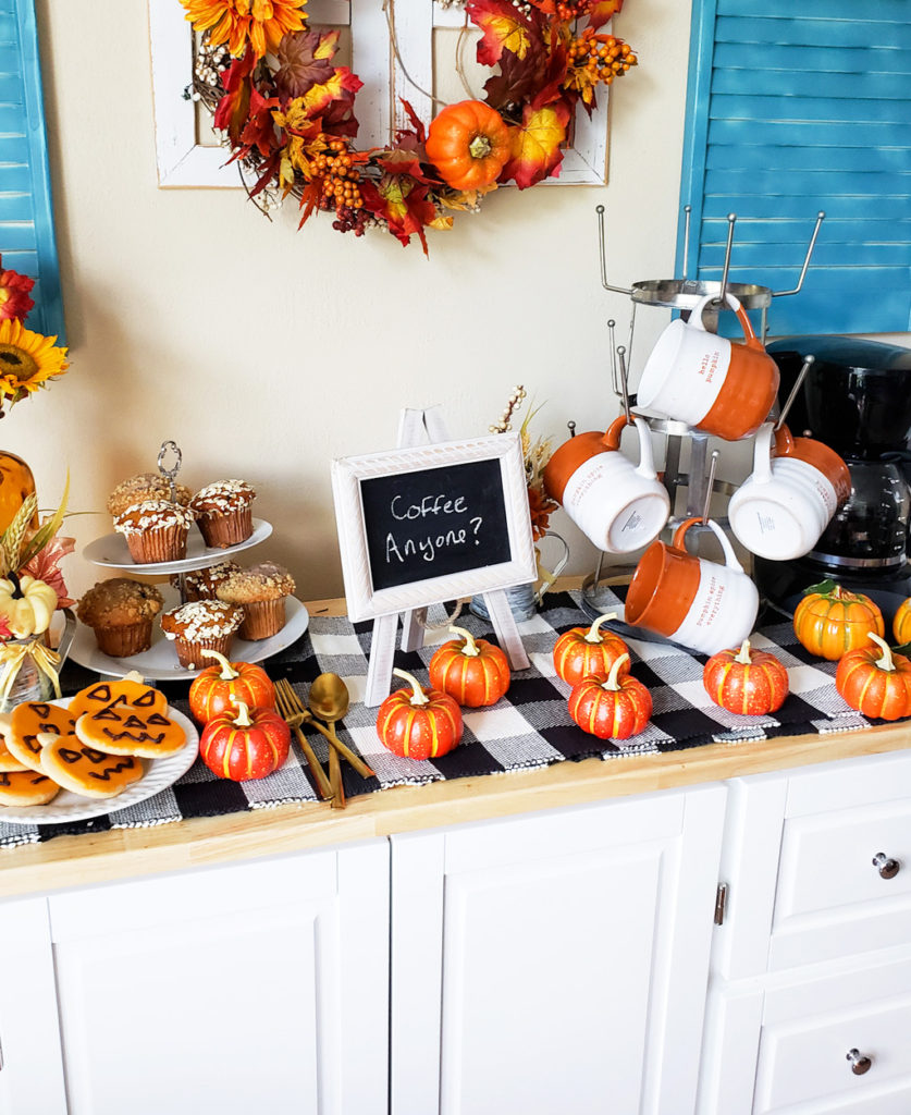 DIY Cozy Fall Coffee Bar, white kitchen island with black and white buffalo plaid table runner, pumpkins, coffee pot, Halloween cookies, and muffins