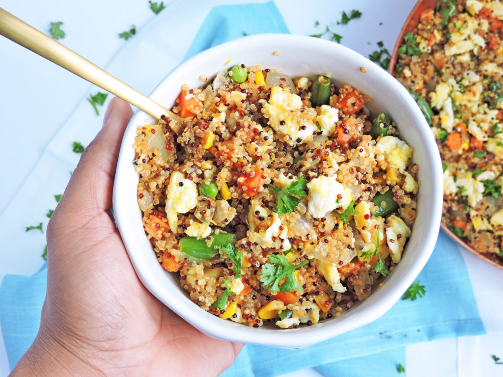Easy Vegetable Fried Quinoa with scrambled eggs, green peas, carrots in a white bowl
