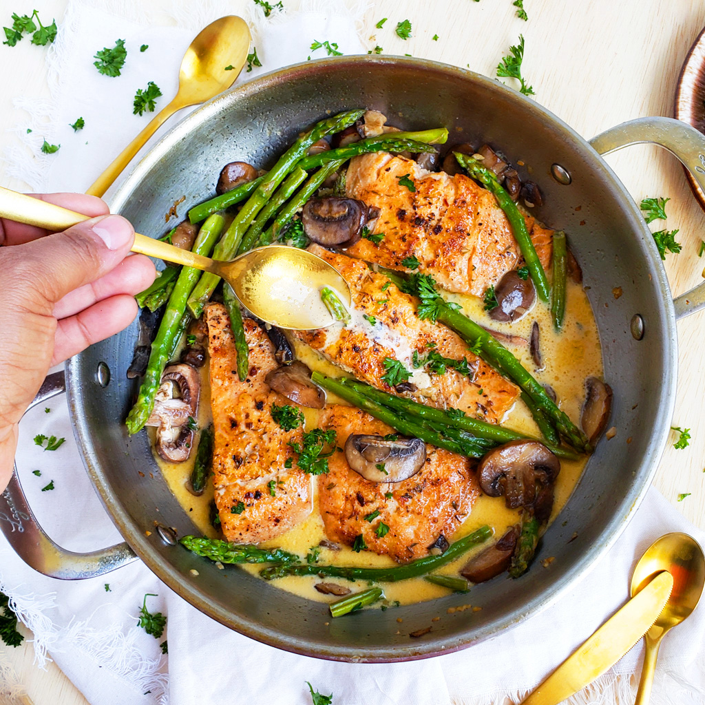 One-Pot Creamy Salmo and asparagus made with garlic and mushrooms in a stainless steel pot
