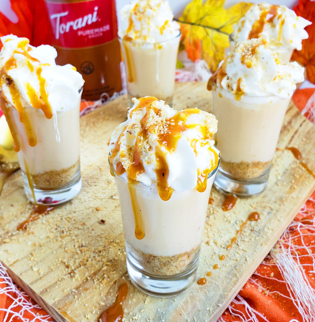 Boozy Pumpkin Pie Cheesecake Shots made with Torani Pumpkin Pie Puremade Sauce in mini shot glasses with with cream and caramel on top