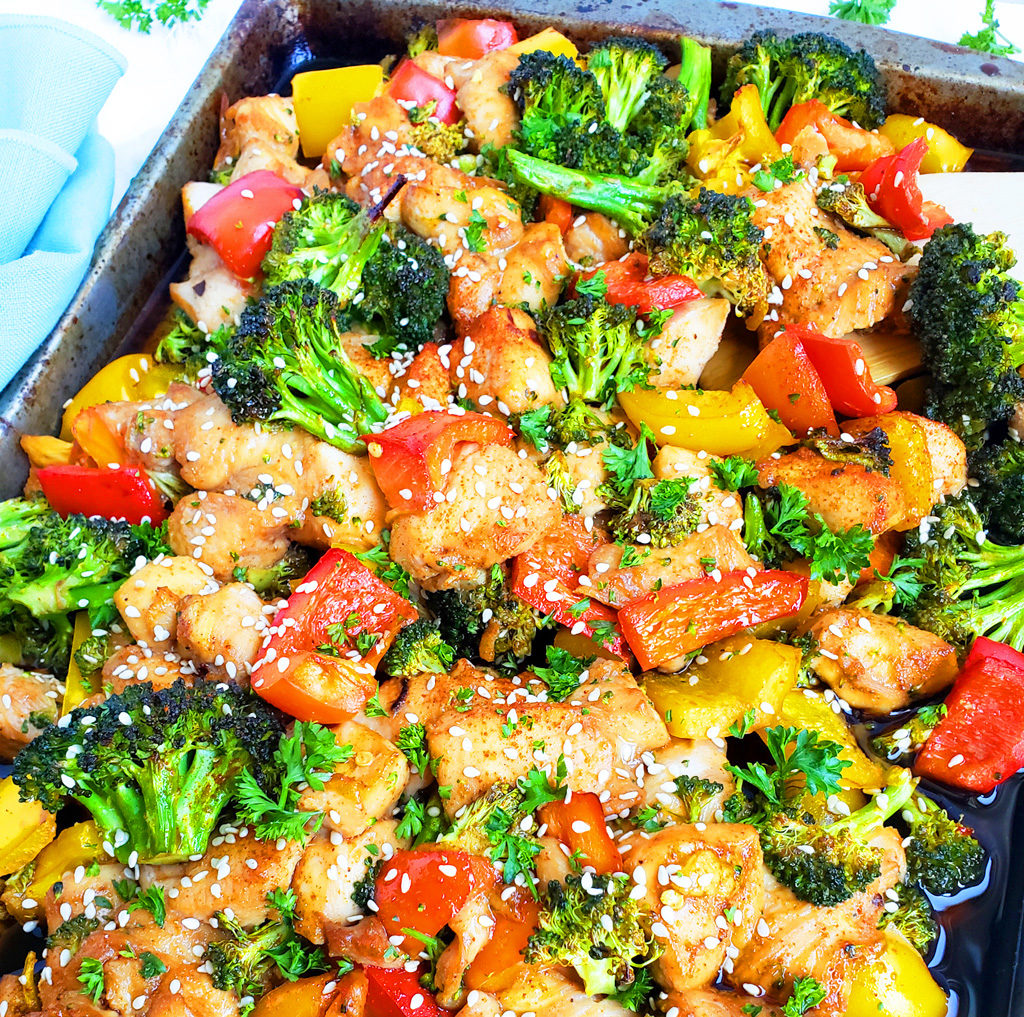 Sheet-Pan Teriyaki Ginger Sesame Chicken & Broccoli with yellow and red bell peppers, broccoli, and chicken on a sheet pan