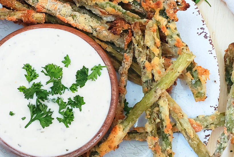 baked asparagus fries with Parmesan cheese on a white plate with a side of ranch dressing