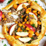 Apple Sausage Butternut Squash Galette made with croissant dough sage, herbs, on a white surface