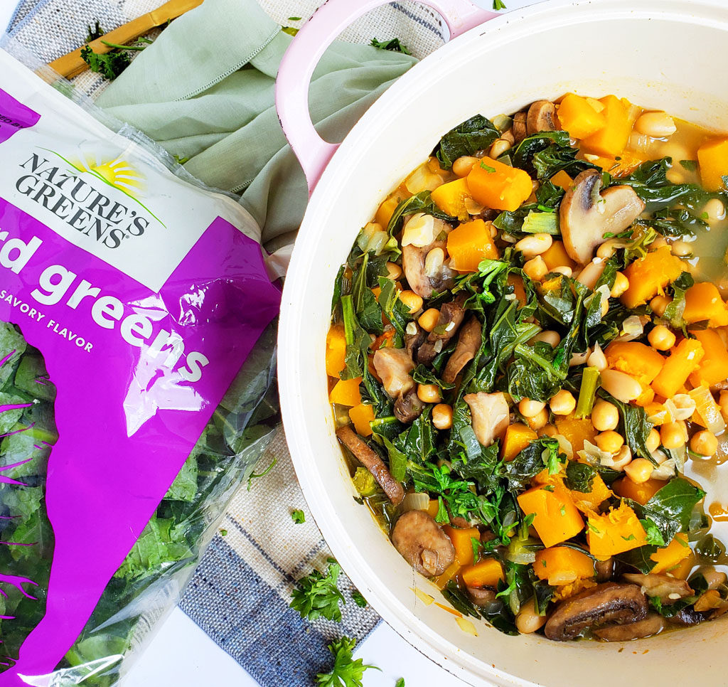 Vegan Butternut Squash, Collard Green & Chickpea Soup in a white pot with a wooden spoon