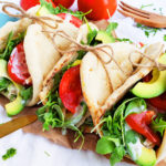 Chicken Avocado Ranch Naan Wraps made with Sprouts Brand Organic Dressing on a whole wheat naan, topped with tomatoes, arugula, and sliced avocado
