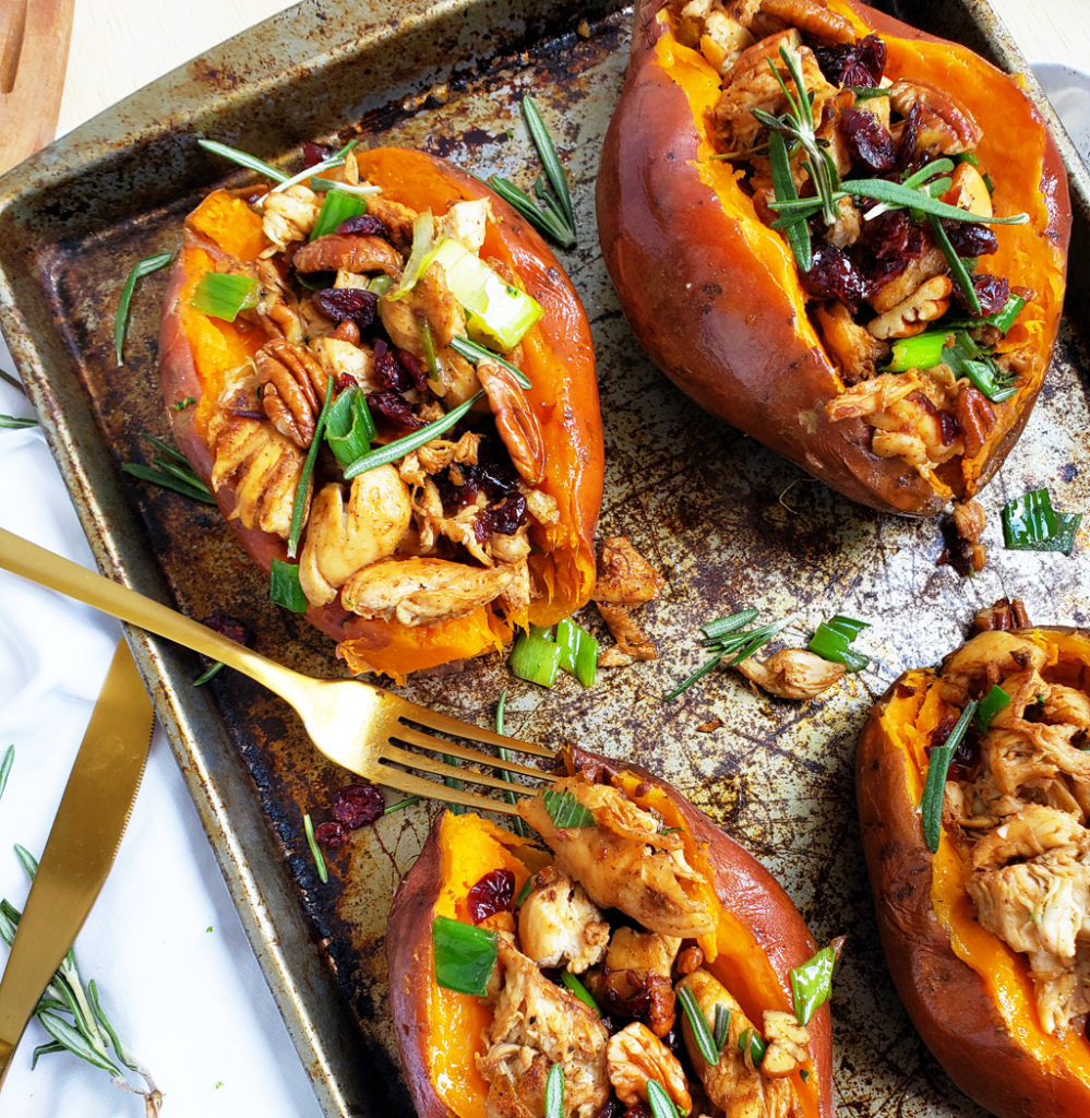 Cranberry Pecan Chicken Stuffed Sweet Potato on a rusted baking sheet topped with dried cranberries, green onions, pecans, chicken and rosemary