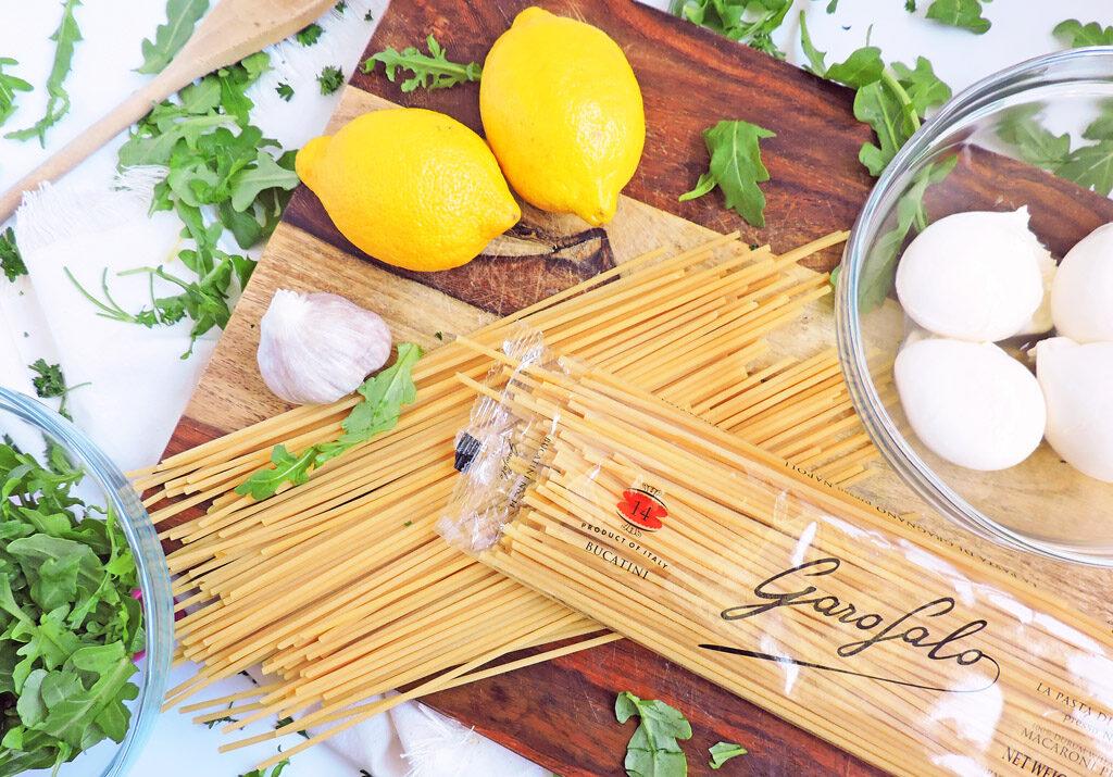 Lemon Garlic Bucatini Pasta with Arugula & Burrata and lemon slices on a white platter
