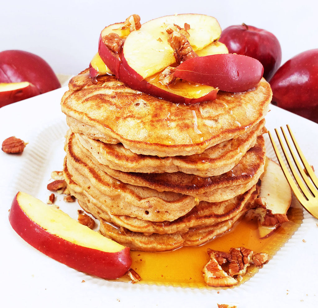 whole wheat apple pecan pancakes stacked on a white plate, topped with red apple slices, pecans, and maple syrup