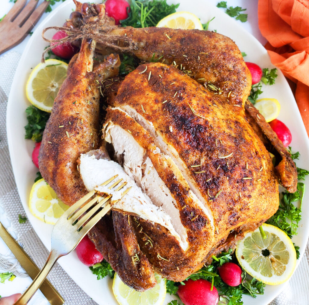 Cajun & Herb Slow-Roasted Turkey, cooked overnight, on a white serving platter