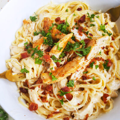 Creamy 3-Cheese Chicken & Garlic Pasta is a quick 30 minute meal served in a white bowl with chicken, bacon, and parsley on top