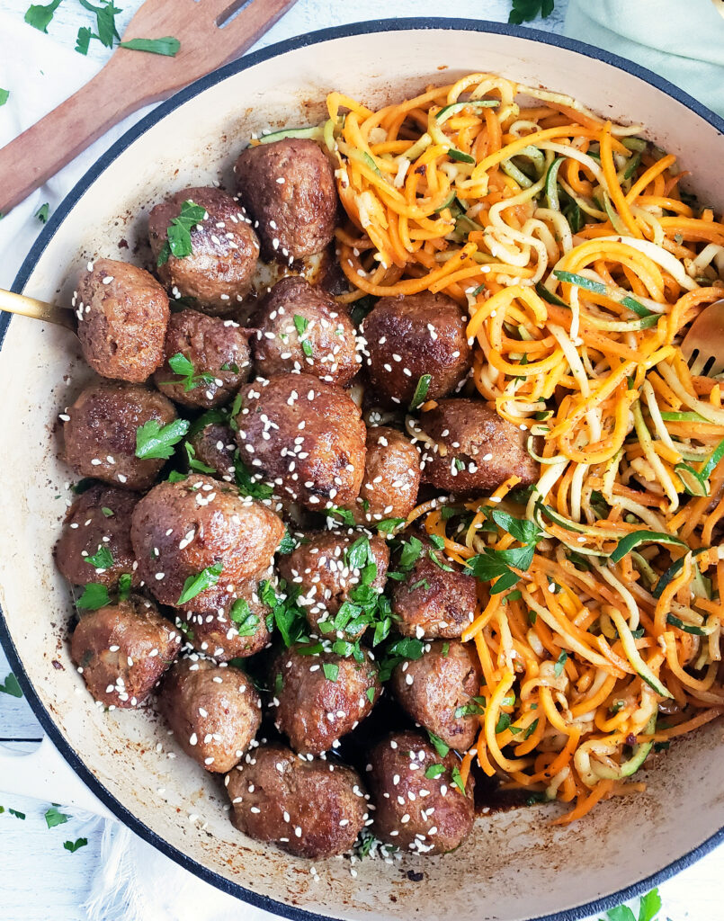 Garlicky Sesame Turkey Meatballs with Zucchini & Butternut Squash Noodles in a white cast iron skillet. It's the perfect healthy meal.