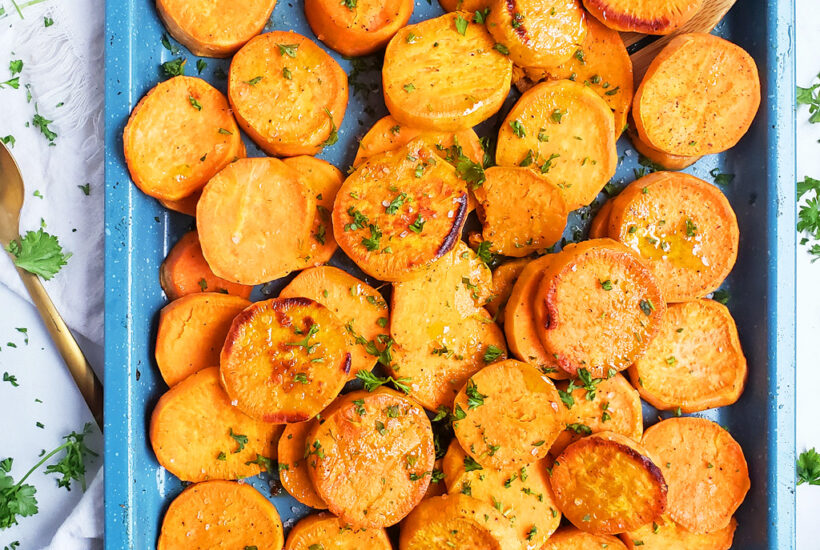 Honey Herb Roasted Sweet Potatoes on a blue baking sheet, topped with rosemary and herbs