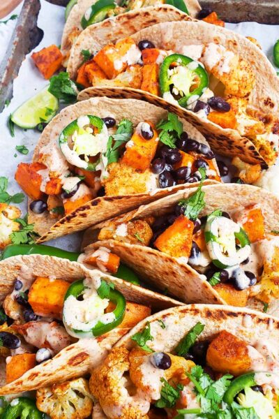 Vegan Roasted Sweet Potato & Cauliflower Tacos made with North Carolina Sweetpotatoes and charred whole wheat tortillas. The perfect plant-based meal for the whole family. #sweetpotatotacos #vegantacos #caulifowertacos #plantbasedtacos #tacos #healthytacos #plantbasedmeals