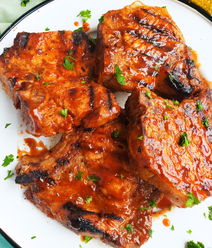 These Spicy Grilled BBQ Pork Chops have the perfect grill marks and a delicious, red barbecue sauce served on a white plate. #porkchops #bbqporkchops beautifuleatsandthings.com