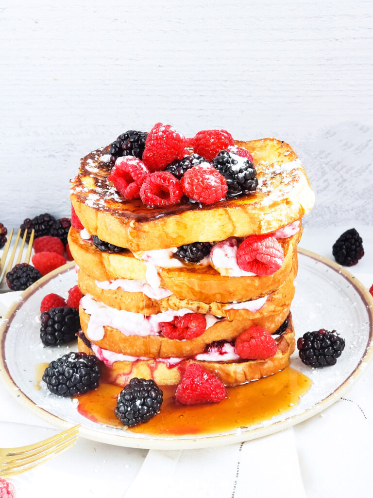 This Berry Cream Cheese Stuffed French Toast is the perfect breakfast solution! Stacked high with layers of berry cream cheese in between, topped with raspberries and blackberries. Beautifuleatsandthings.com