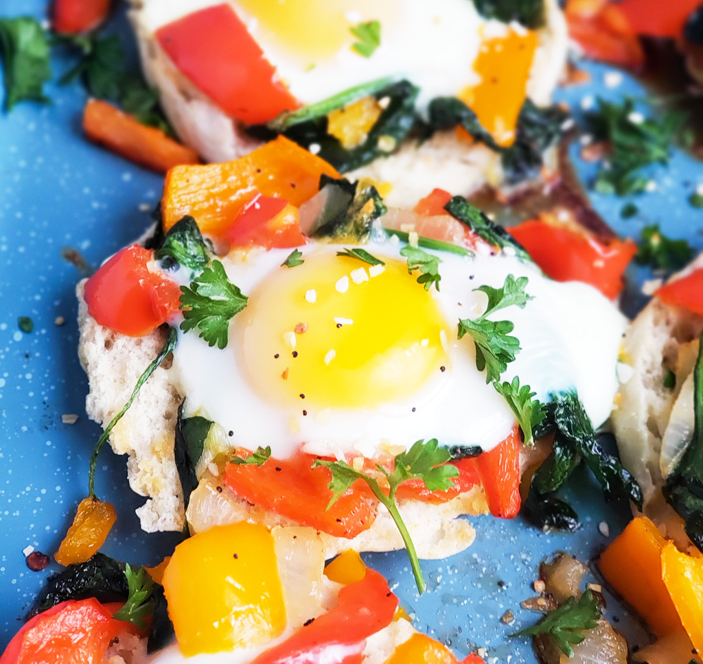 These Mini Egg & Veggie Breakfast Pizzas elevate breakfast on weekday mornings and make a quick weeknight dinner too. Mini English Muffin vegetable and sunny-side up eggs pizza on a blue sheet pan. Beautifuleatsandthings.com