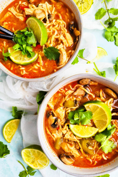 On those cool Fall nights, warm up with this delicious Spicy Slow Cooker Pad Thai Chicken & Ramen Soup. made with ramen noodles topped with lime and cilantro beautifuleatsandthings.com