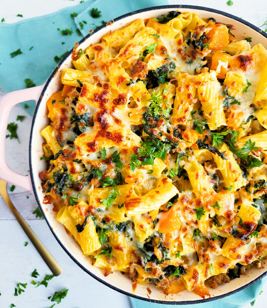 Try this delicious Garlicky Kale Sausage & Butternut Squash Pasta Bake, made with rigatoni noodles, kale, butternut squash, sausage in a pink Dutch oven. beautifuleatsandthings.com