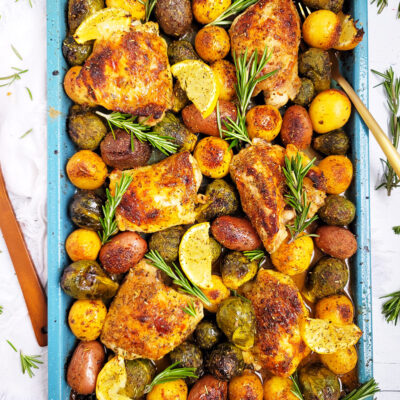 This Lemony Rosemary Sheet Pan Chicken with Brussels Sprouts & Potatoes the perfect weeknight meal; made on a blue sheet pan with chicken thighs, roasted potatoes, Brussels sprouts, lemon wedges and rosemary. beautifuleatsandthings.com