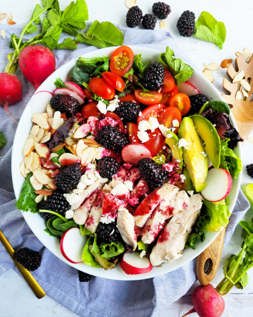 This Blackberry Balsamic Avocado Chicken Salad contains fresh blackberries, avocado, feta, grilled chicken, sliced grape tomatoes, sliced almonds and a blackberry vinaigrette dressing. Served in a white bowl. Beautifuleatsandthings.com