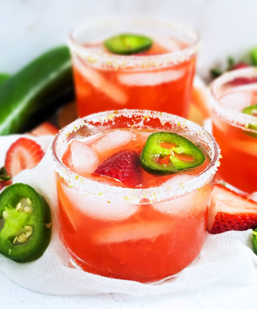 Warm and sunny weather means that it's time for refreshing cocktails, such as this Spicy Strawberry Jalapeño Margarita! It's the perfect treat for Cinco de Mayo. made with fresh strawberries, jalapenos, agave nectar, lime juice in a short glass topped with strawberries and jalapeno slices. With a sugar and salt rim, with lime zest.  beautifuleatsandthings.com