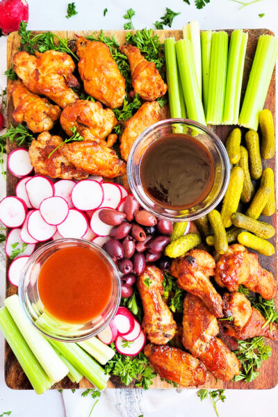 So, the next time you're expecting company, put together this Chicken Wing Charcuterie Board made with party wings, radishes, pickles, celery, and olives on a wooden board. beautifuleatsandthings.com