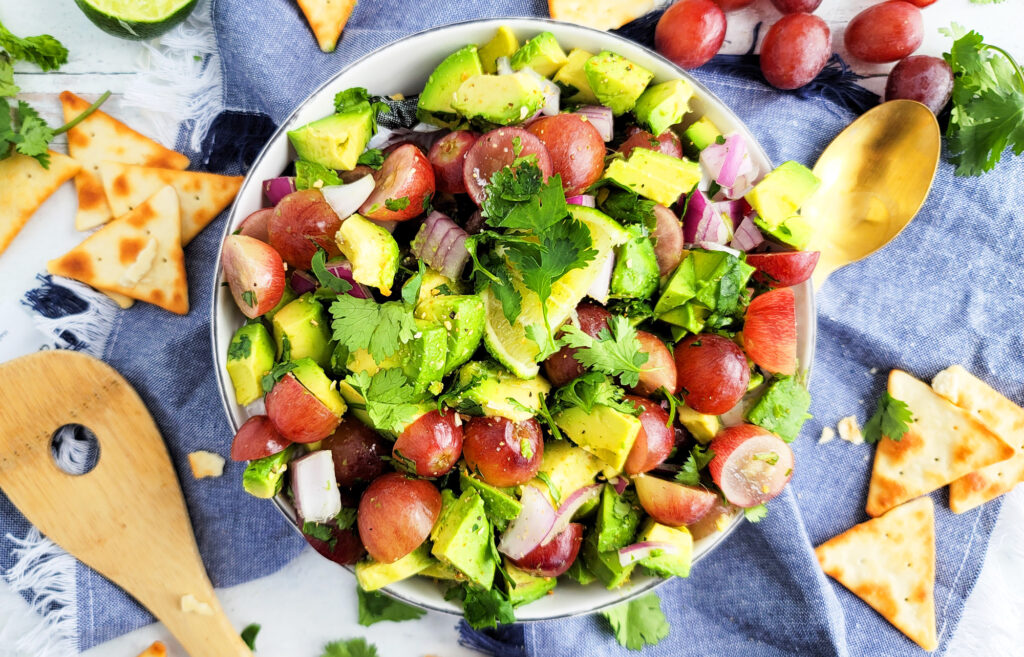 Grape and avocado salsa made with red California grapes, red onions, avocado, lime and cilantro in a white bowl. beautifuleatsandthings.com