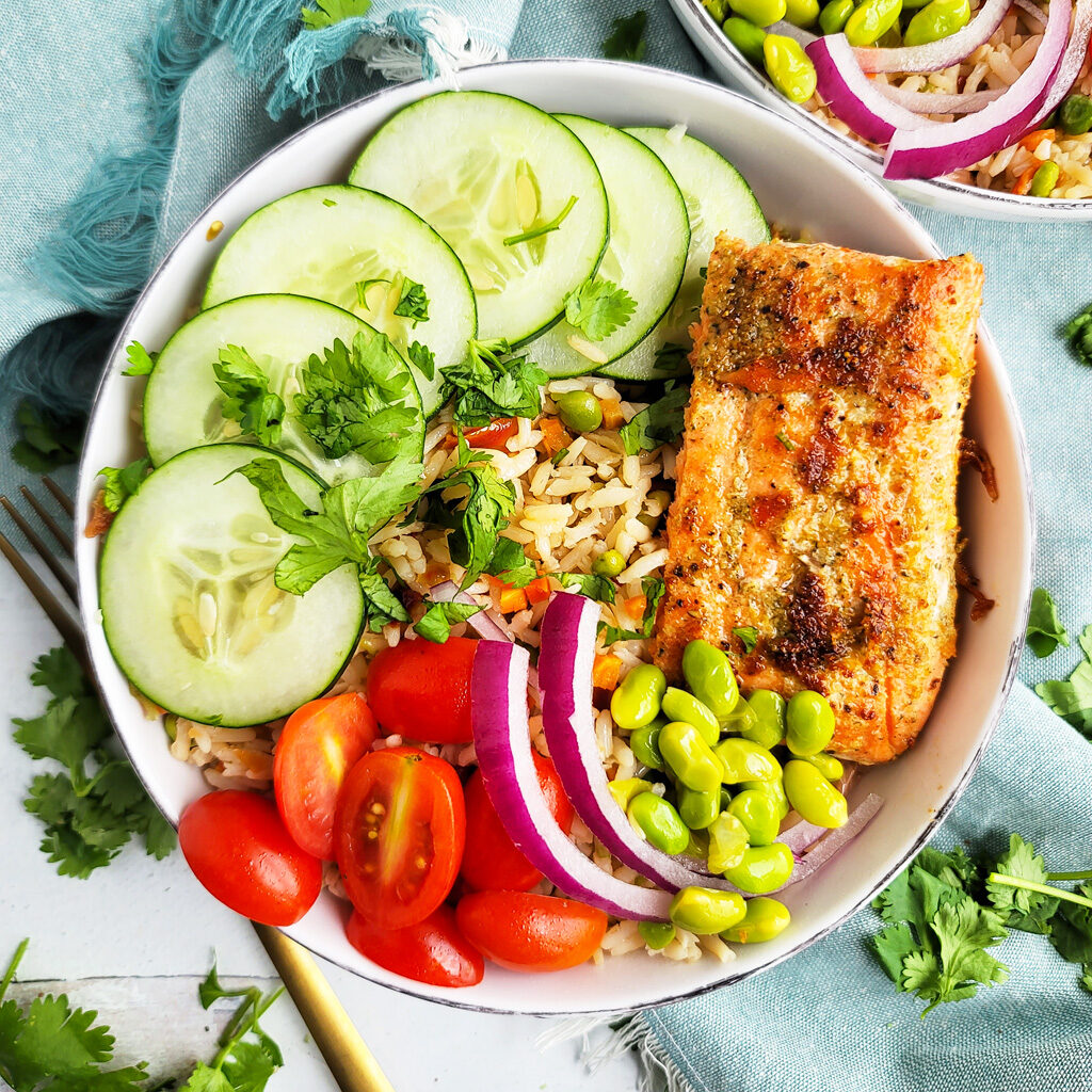 This Spicy Tahini Salmon Garden Rice Bowl is made with Success Garden Rice Blends, sliced cucumbers, edamame, grape tomatoes, red onions, and salmon; served in a white bowl  beautifuleatsandthings.com