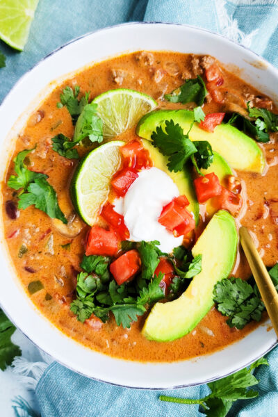 This Slow Cooker Creamy Taco Soup recipe imade in the crockpot, served in a white bowl and topped with lime wedges, tomatoes, cilantro, and avocado beautifuleatsandthings.com